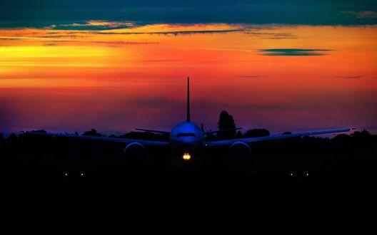 Обои Самолет летит на фоне яркого закатного неба над сгущающейся снизу темнотой