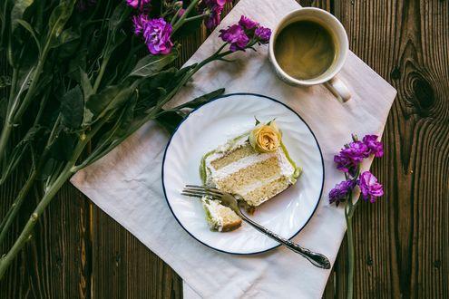 Обои Чашка кофе, кусочек тортика на блюдце и цветы на столе