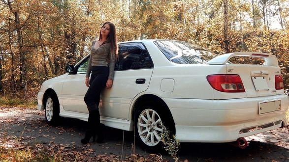 Обои Стройная симпатичная девушка брюнетка с длинными волосами стоит рядом с авто на фоне осеннего парка с облетающей листвой