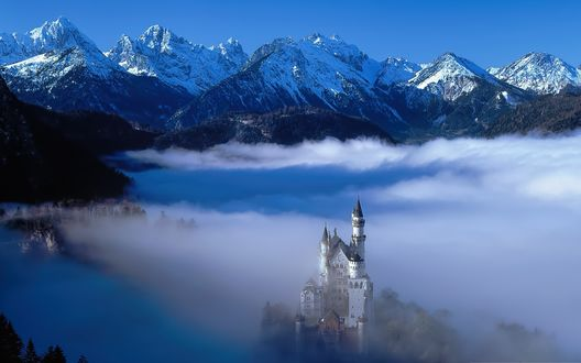 Обои Замок Нойшванштайн, Германия в тумане на фоне снежных гор