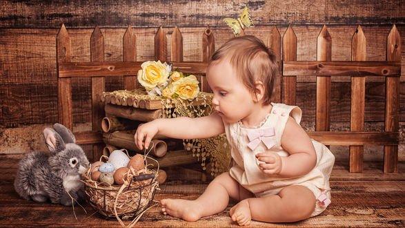 Обои Маленькая девочка сидит рядом с корзинкой яиц и плюшевым зайцем