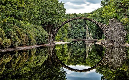 Обои Полуразрушенный арочный мост Rakotzbrucke Devils Bridge in Gablenz, Germany / Дьявола Ракоцбрюке в Габленце, в Германии через реку, заросшую лесом, отражается в воде