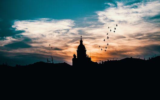 Обои Силуэт церкви на фоне сгущающейся над холмами темноты и неба, подсвеченного закатом