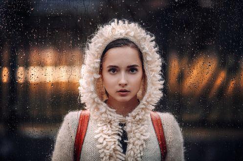 Обои Девушка в куртке стоит на фоне окна, покрытого каплями от дождя