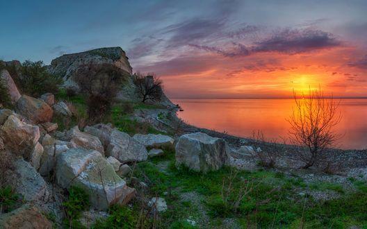 Обои Каменистый морской берег на фоне заката