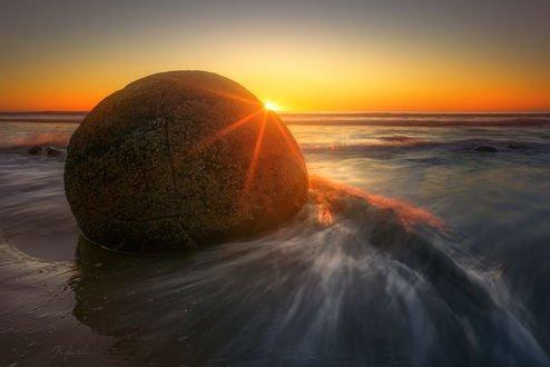 Обои Солнце выглядывает из-за валуна Моеракі / Моераки, на Koekohe Beach / пляже Коекохе в регионе Otago / Отаго на юго-восточном побережье Южного острова New Zealand / Новой Зеландии, фотограф Kane Hartill
