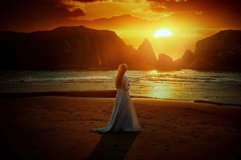 Обои Девушка в длинном платье стоит на побережье на фоне заката, фотограф TJ Drysdale