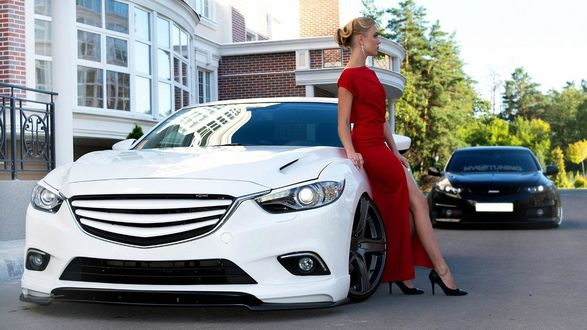Обои Стройная симпатичная блондинка в вечернем платье стоит у авто на фоне здания и природы