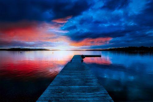 Обои Розовые и голубые облака отражаются в воде с деревянным помостом, уходящим в глубь озера
