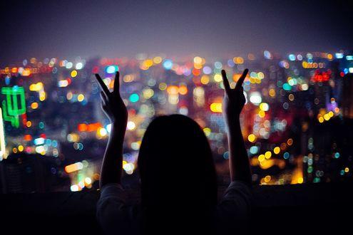Обои Девушка показывает знак руками на фоне ночного города