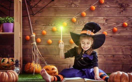 Обои Девочка в костюме ведьмы склонилась со свечой над магической книгой в окружении хэллоуинских тыкв