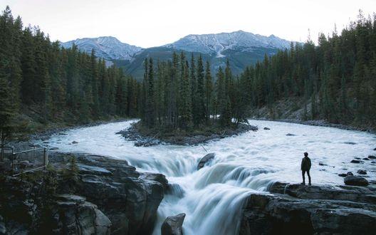 Обои Мужчина на краю водопада на горной реке с островком посередине, заросшим хвойными деревьями, вдали виднеются заснеженные вершины