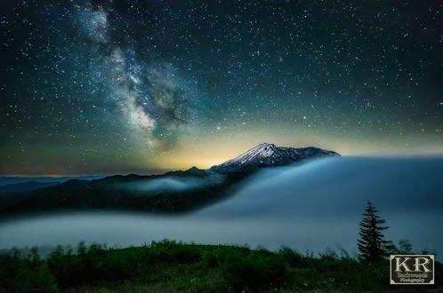 Обои Северное сияние над горой, окутанной густым туманом, фотограф Kevin Russell