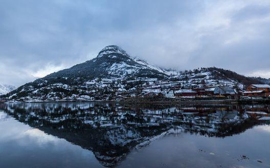 Обои Небольшое селение у подножья заснеженных гор отражается в водах озера под потемневшим холодным небом
