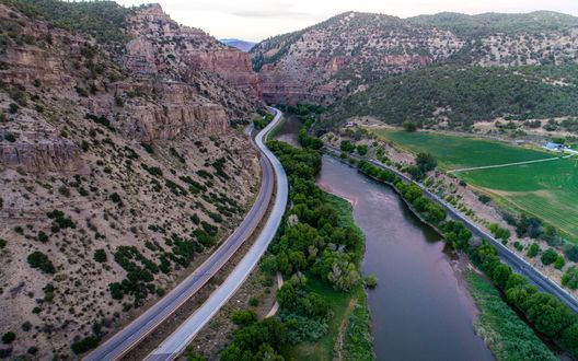 Обои Извилистое шоссе тянется между рекой и отвесной горой, внизу расстилается зеленая долина, впереди смыкаются горы
