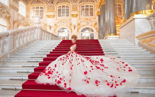 Обои Девушка в белом бальном платье с красными цветами стоит на широкой мраморной лестнице во дворце