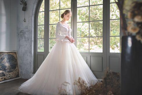 Обои Девушка в белом бальном платье стоит у окна с видом на сад