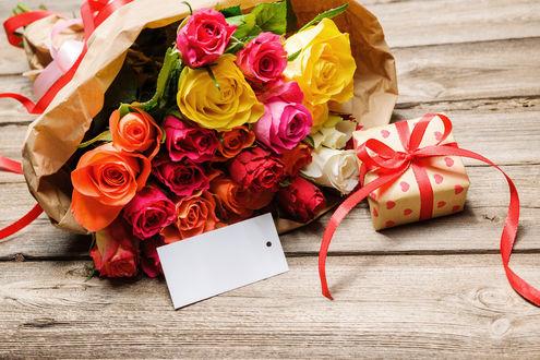 Обои Букет из разноцветных роз в бумажной обертке с подарочком и открыткой на деревянной поверхности