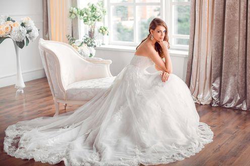 Обои Невеста в свадебном платье сидит на кушетке в гостиной