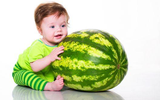 Обои Маленький голубоглазый мальчик в зеленой полосатой одежде с огромным полосатым арбузом в руках