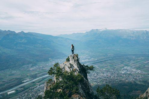 Обои Девушка на вершине одинокой поросшей зеленью скалы над горной долиной