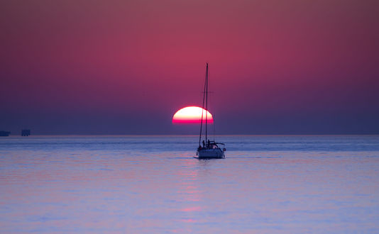 Обои Лодка с людьми на воде на фоне заката, фотограф Ricardo Mateus