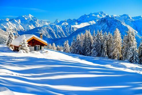 Обои Одинокий деревянный домик зимой в горах на фоне голубого неба