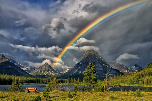 Обои Деревянная лавочка на берегу пруда на фоне природы, гор, сумрачного неба и радуги, фотограф Philip Kuntz