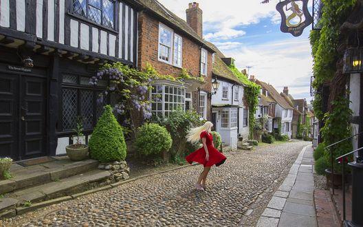 Обои Светловолосая девушка в красном платье стоит на улице среди домов
