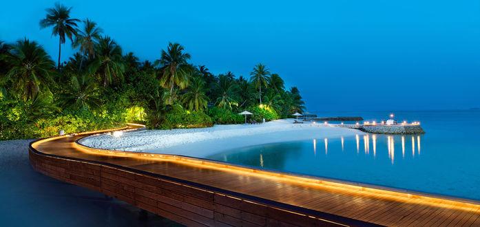 Обои Деревянный настил в океане с подсветкой на фоне вечерней экзотической природы и безоблачного неба