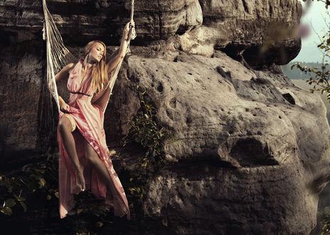 Обои Девушка в розовом платье в гамаке висит на скале на фоне природы
