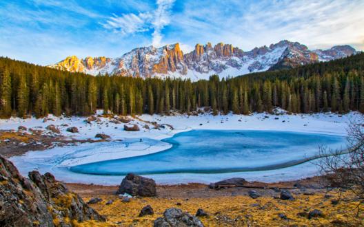 Обои Небольшое замерзшее озеро возле леса и заснеженных гор