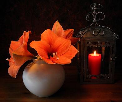 Обои Оранжевые лилии стоящие в вазе, на столе, рядом с горящей свечой в подсвечнике