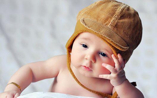 Обои Ребенок в коричневой шапочке на постели