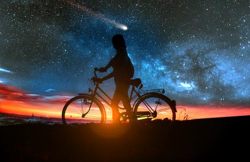 Обои Девушка с велосипедом в последних лучах заходящего солнца стоит на фоне ночного неба и падающей звезды