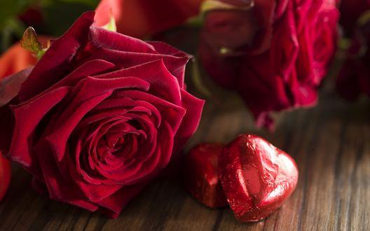 Обои Две конфеты в форме сердечка лежат возле красных роз