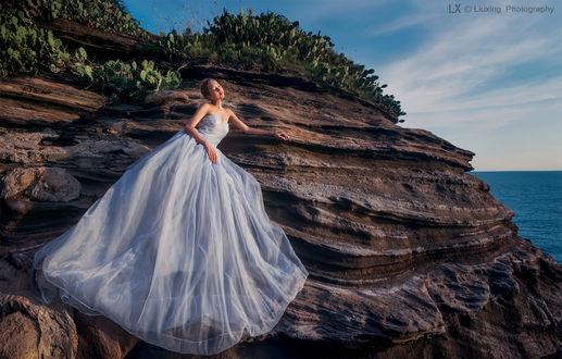 Обои Девушка в длинном пышном платье стоит на скале
