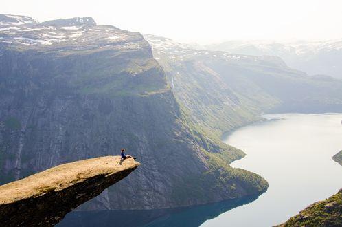 Обои Девушка сидит на краю скалы с видом на горы и реку