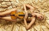 Обои Девушка со скрипкой лежит на золотой поверхности
