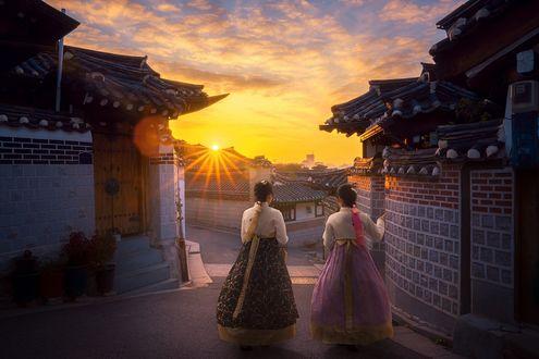 Обои Две корейские девушки в ханбоках любуются рассветом, стоя на улочке старого города