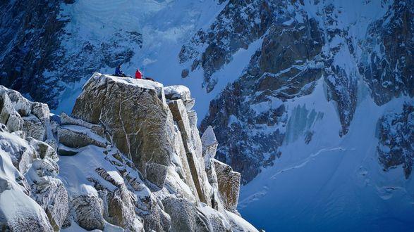 Обои Туристы на заснеженной скальной площадке посреди гор
