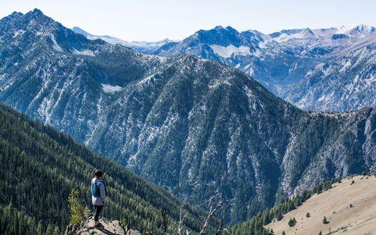 Обои Девушка на горном выступе, затерявшемся среди бескрайних гор