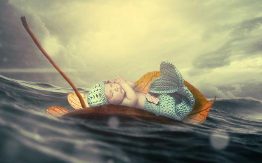 Обои Спящий младенец в костюме русалки плывет на листке по волнам