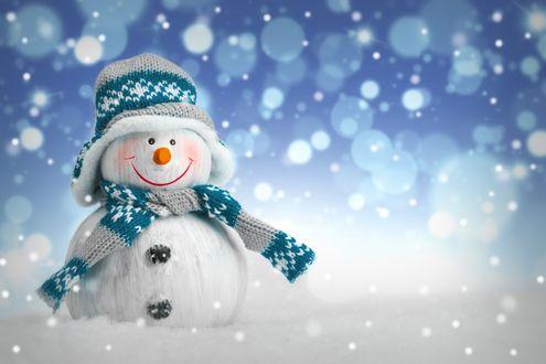 Обои Снеговик в шапке и с шарфиком стоит на снегу