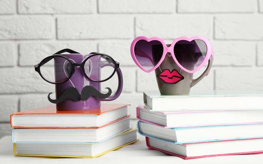 Обои Две смешные чашки в очках стоят на стопках книг