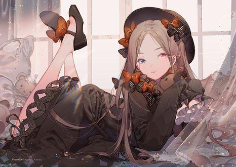 Обои Девочка с разными глазами в черном платье и шляпе лежит на кровати с игрушками у окна