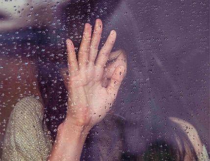 Обои Девушка держит руку на стекле с каплями от дождя