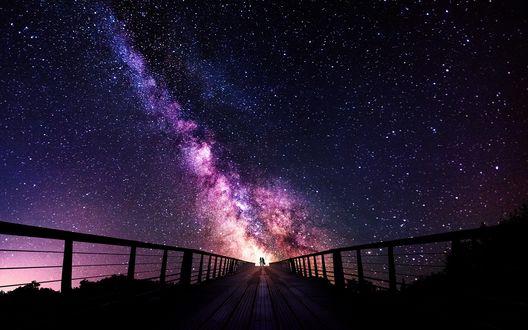 Обои Силуэт пары на мосту, на фоне сияния в звездном небе, фотограф Sebastien Gaborit