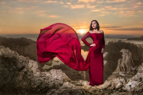 Обои Брюнетка в платье цвета красного вина позирует на скалах, на фоне заходящего солнца, by Eric Champs Sudistenews