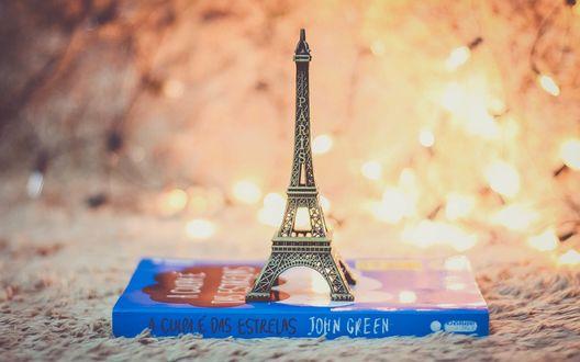 Обои Фигурка Эйфелевой башни стоит на книге возле горящей гирлянды